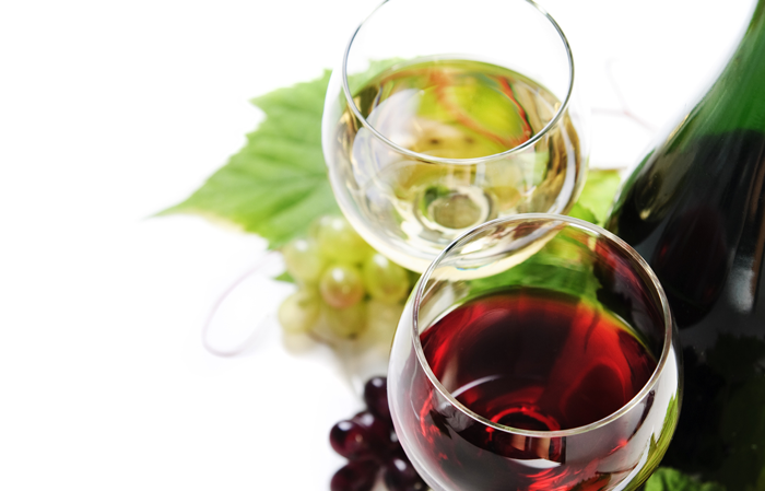 overhead shot of two glasses of wine. one red and one white with wine leaves under the glasses.