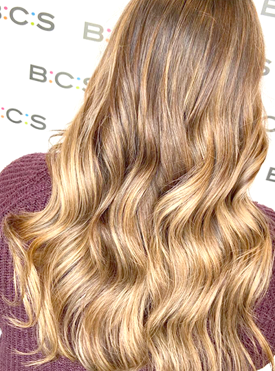 womans head from the back with brown wavy blowdryed hair, BCS banner in the background