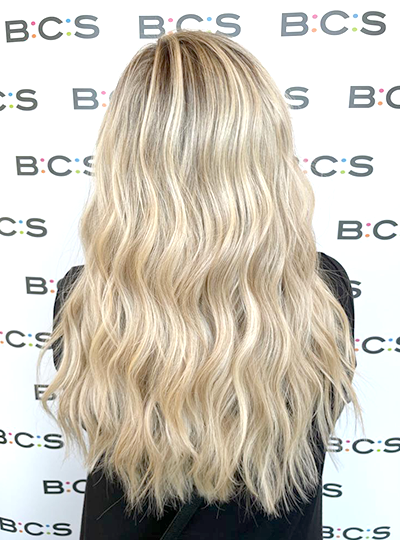 back of woman's head with blonde hair. BCS printed roller banner in background