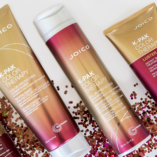 Three Joico products laid in a line at an angle with glitter around the bottom of each product