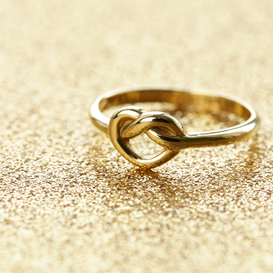 gold ring with a heart as the main loop laid on a sparkly gold background