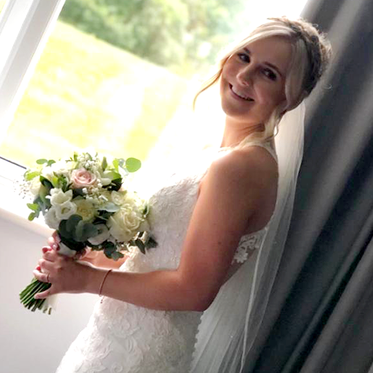 bride stood in a window looking at the camera holding a bouquet and smiling