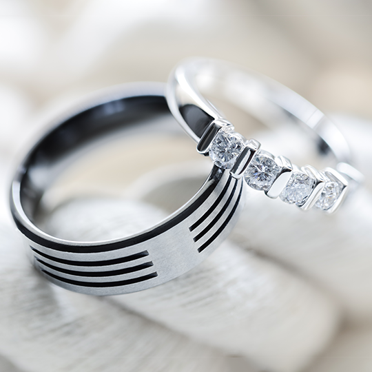 set of platinum wedding rings with the brides ring laid on the edge of the grooms ring