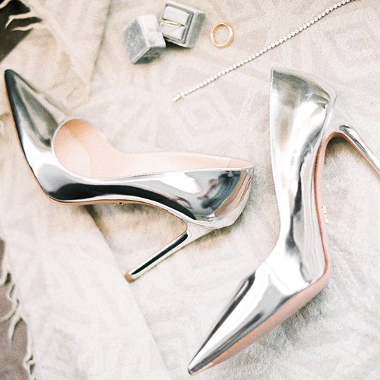 silver high heels on a bed with silver necklace and ring