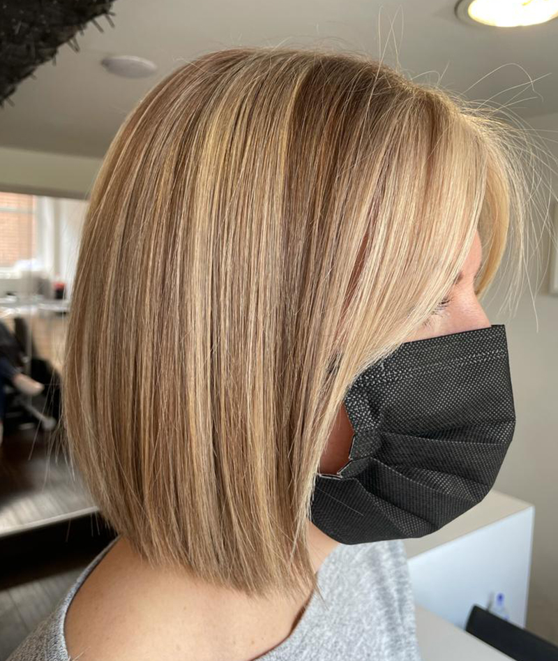 blonde bob profile shot, wearing a black mask inside the salon with the wash basins blurred in the background