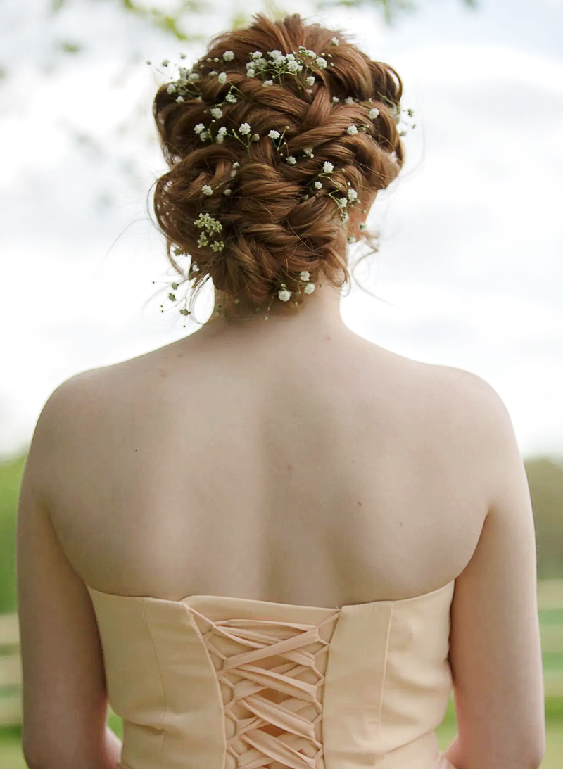 Red wedding hair photo from the back. Hair up with subtle flowers weaved through it.